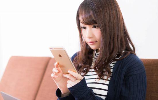 スマホアプリで動画を見る女性