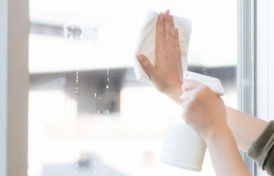 窓を拭く女性の腕