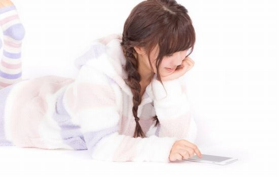 寝転びながらスマホアプリで遊ぶ女性